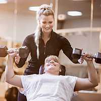 Personal training. Woman lifting dumbbells with trainer.