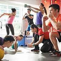 Women and men performing different exercises. Circuit classes.